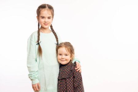Horizontal shot of small girl embraces older sister with love, missed her very much, wants to play together, glad to have each other, look alike, have truthful friendship.