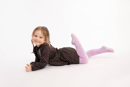Happy smiling girl in dress lying on her stomach isolated over white background Stock Photo