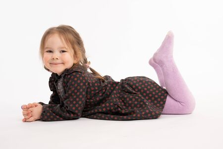 Happy adorable redhead little girl in dress smiling and looking at the camera while liying on the ground