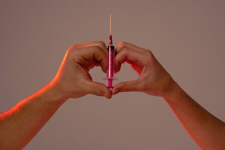 Male and female hands holding pink syringe together while showing heart, love sign, grey wall on the background, 26 June, International Day Against Drug abuse. Stok Fotoğraf