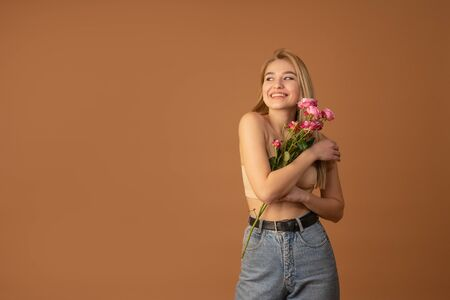 Young cheerful blonde female with pleasant charming smile hugging ping flowers and looking at left side, isolated over orange background