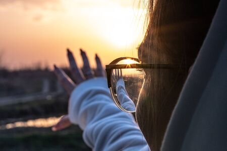 Attractive woman in glasses enjoys a sunset, reaching to the sun