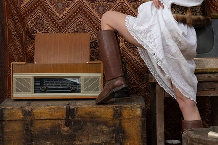 Young female in national white dress and old leather shoes puts her leg on the aged chest near old radio