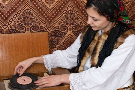 Waist up photo of attractive female in national white dress who puts vinyl in old retro record player