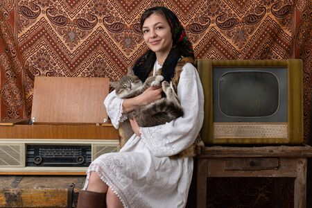 Cheerful female in national white dress sitting near the old retro radio and tv, holding cat in her hands and looking at the camera Banque d'images