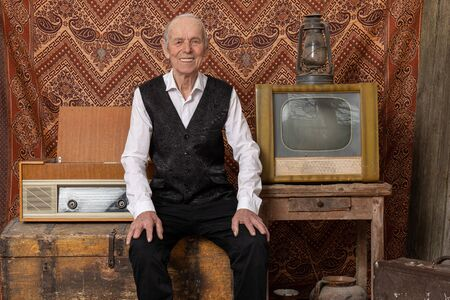 Happy old man in elegant clothes sitting on the aged chest near retro tv, radio and old gas llamp, smiling and looking at the camera