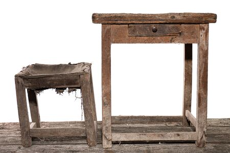 Very old wooden shoemaster's workplace, vintage table and chair in the dust, isolated over white background