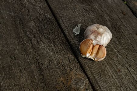 Head of garlic, a few cloves of garlic. They lie on the surface of brushed pine boards. Copyspace 版權商用圖片