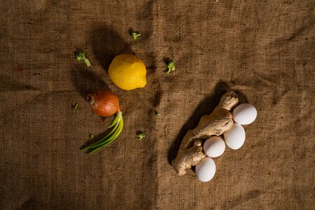 Healthy food concept. Top view of a ginger with chicken eggs and lemon with green onion