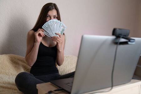 Young charming woman holding fan of cash money in dollar banknotes, sit and work at bed at home with pc laptop.