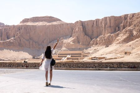 Young brunette female in white dress walks in front of part of the Mortuary temple of the Queen Hatshepsut Dayr el-Bahari or Dayr el-Bahri , Western Bank of the Nile, vacation travel concept