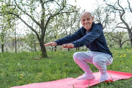 Grandfather pensioner. Active sport workout for old person. Sport and retirement concept. Senior man exercising on pink yoga mat.