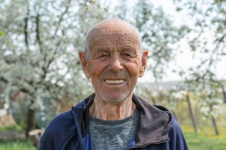 Close up portrait of a happy old man pensioner in sportswear who smiling and looking at the camera