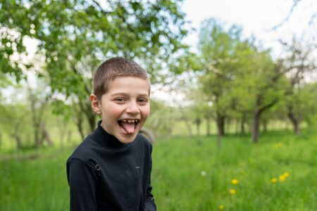 Happy little boy in black shirt shows tongue to the camera