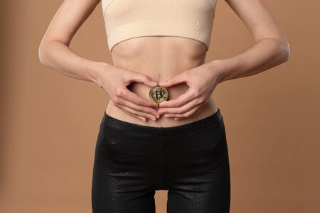 Cropped photo of slim female in beige bra and black pants who holds bitcoin golden coin in her hands on her stomach Banco de Imagens