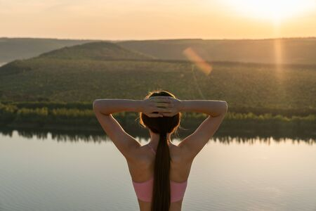 Waist up portrait of a beautiful sporty brunette female who stands back to the camera holds her hands on her head and enjoying sunset behinde the river, summer time Фото со стока
