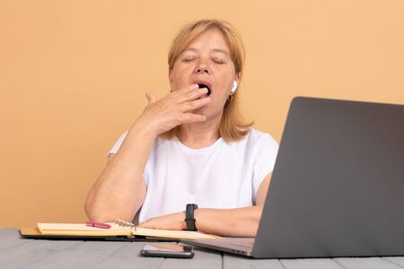 Middle age senior woman sitting at the table at home working using computer laptop bored yawning tired covering mouth with hand.