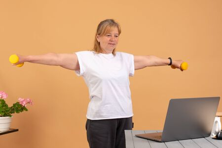 Fit woman doing home workout. Laptop computer with online gym training course. Happy fitness senior female watching exercise video. Personal trainer on the internet. Healthy diet program