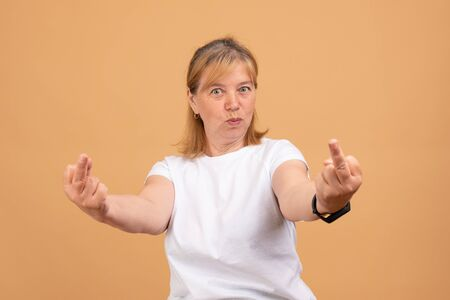 Funny blond woman in white t-shirt showing middle finger, scrooge you, you