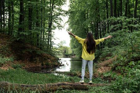 Young woman balances on a tree log near the lake