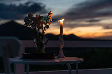 Minimalistic table setting for holiday romantic dinner, wooden table with flower and white candele. Selective focus Standard-Bild