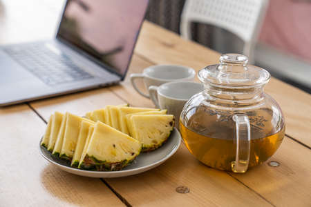 Home office workplace with open laptop, sliced pineapple and a tea mug on wooden desk Standard-Bild