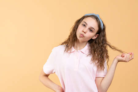 Attractive teen girl touching her curly hair looking at the camera, sending air kiss, studio portrait