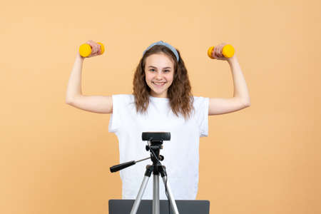 Happy girl blogger stands in front of the camera with dumbbells and a laptop and shoots video on camera as she does exercises at home