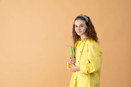 Positive schoolgirl carries spiral notepad, notebook, ready for school and lessons, wears casual clothes, prepares for final examinations, smiles Standard-Bild