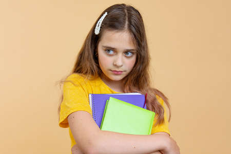 Unhappy european american girl teen student in casual clothes hold books isolated on orange wall background studio portrait. Education in high school university college concept