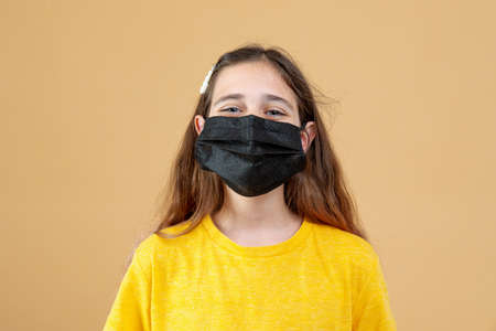 Masked child - protection against influenza virus. Little Caucasian girl wearing mask for protect pm2.5. Biological weapons. baby on an orange background with copy space. Epidemic, pandemic