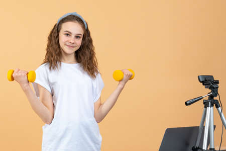 Strong confident beautiful fitness teen girl giving fitness advice on her vlog