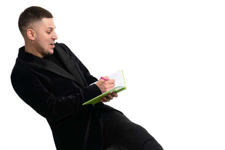 Young happy businessman making notes in a notebook