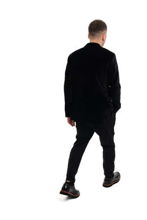 Back view of a young business man walking, isolated on white background