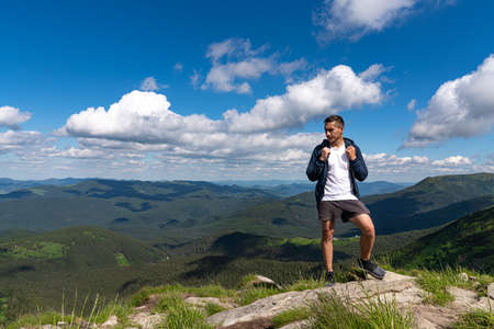 Excited man hiking on a mountain top with backpack enjoy the view and looking for adventures