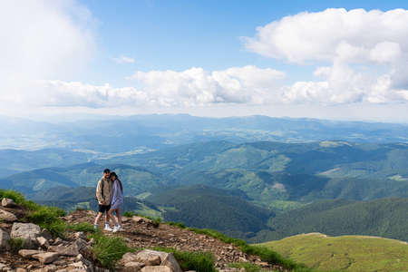 Young happy couple on top of hill and enjoying mountains view Standard-Bild