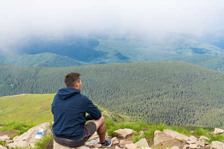 Side view young man hiker sitting on mountain`s top enjoying rocks landscape background. Travel lifestyle wanderlus