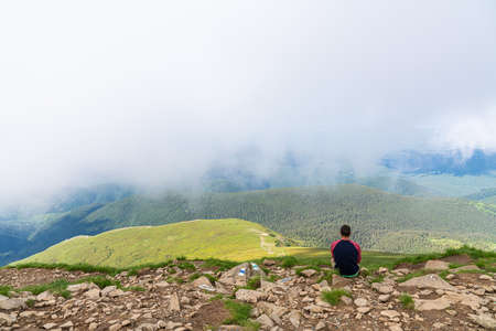 Young man hiker watching the beautiful pensive dreamy magical mountain landscape. Time for reflection Standard-Bild