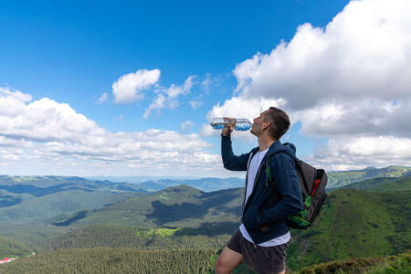 Hiker relaxing on top of the mountain and drinking bottled water Standard-Bild