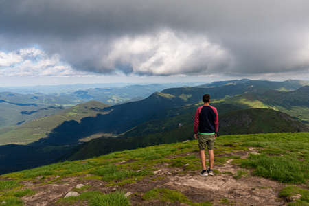Traveler standing on high mountain cliff, enjoying scenery on mountain top. Pov view. Hiking freedom concept