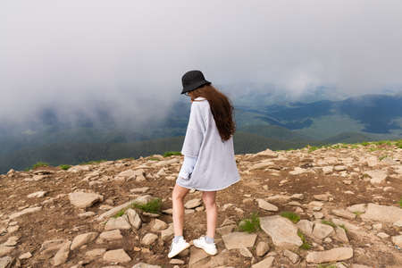 Adventurous Female Hiker on top of a mountain covered in clouds