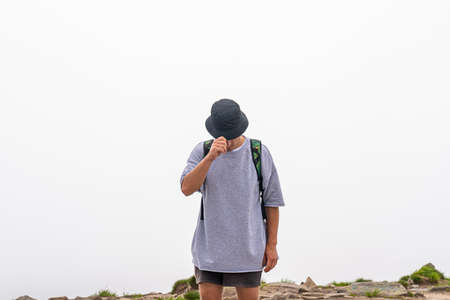 A man with backpack standing on mountain top, with clouds and fog on the background Standard-Bild