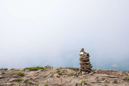 Stack of stones on top of a mountain on clouds background. Concept of balance and harmony