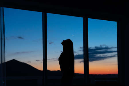 Silhouette of a girl against sunset on the window mountains view