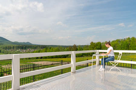 Concentrated stylish woman sitting on the white terrace balcony in a laptop apartment and working, staring intently at the screen. Beautiful girl freelancer working at a laptop in a country house