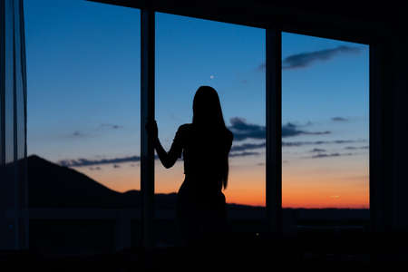 Silhouette of a back of a girl standing near the window and looking through the window dreaming or thinking