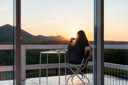 Woman holds cup of tea in her hands at mountain resort. Silhouette of a girl with hot coffee mug at wooden balcony of country house. Forest and mountains on background Standard-Bild
