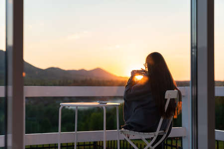 Young beautiful woman enjoys the tea with herbs on the terrace of a cafe in the mountains on a sunnset
