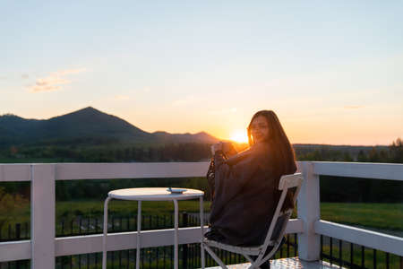 Young Woman Relaxing On Roof Terrace With Cup Of Coffee Standard-Bild