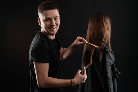 Handsome young hairstylist smiling at camera while combing hair to beautiful young woman in beauty salon
